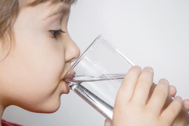 Il bambino tiene un bicchiere d'acqua nelle sue mani. messa a fuoco selettiva.