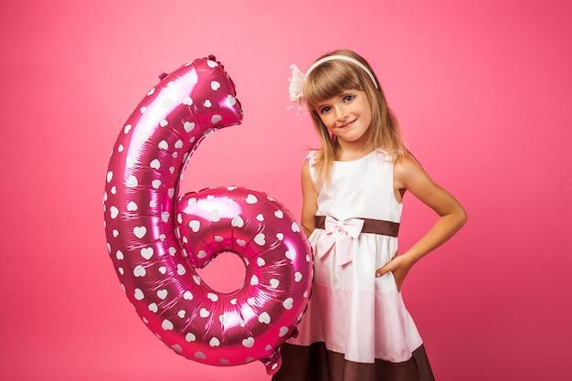 Il bambino tiene un palloncino nello stile del numero 6