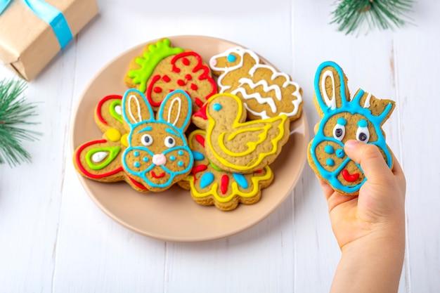Il bambino tiene un pan di zenzero (biscotto) su uno sfondo di legno bianco tra rami di abete e coni. concetto di regalo dolce di natale e capodanno.