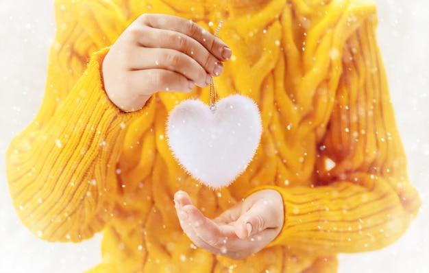 Il bambino tiene una decorazione di natale e regali su uno sfondo bianco. messa a fuoco selettiva