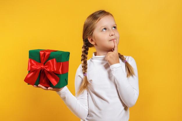 Il bambino tiene una scatola con un regalo e sogni.