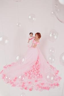 Il bambino tra le braccia di sua madre in un vestito rosa di fiori