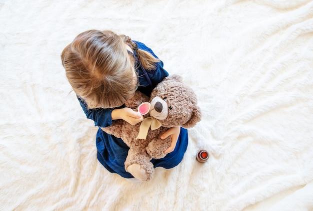 Il bambino tratta un orso. il gioco del dottore. messa a fuoco selettiva