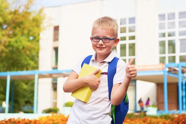 Il bambino va alla scuola elementare. ritratto di un bambino felice con una valigetta sulla schiena.