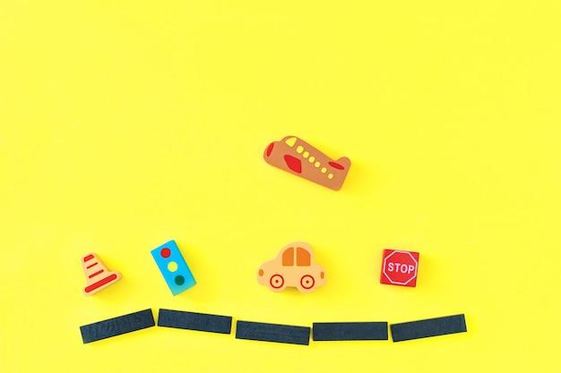 Il bambino variopinto scherza i giocattoli di legno su fondo giallo. sviluppare blocchi colorati, automobili e aerei. vista dall'alto. disteso. copia spazio per il testo