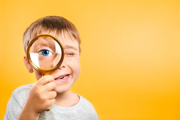 Il bambino vede attraverso la lente d'ingrandimento sugli sfondi di colore giallo.