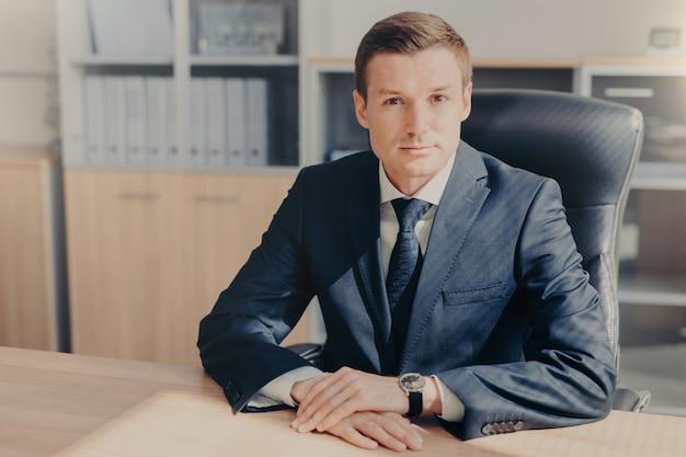 Il banchiere maschio professionista siede nel gabinetto, indossa abiti formali