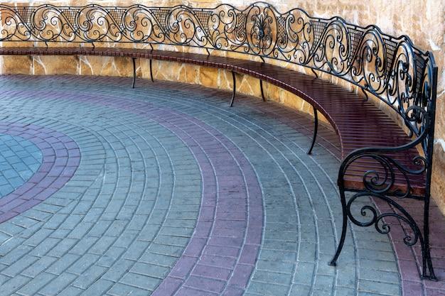 Il banco metallico forgiato openwork sta sul marciapiede nel parco della città.