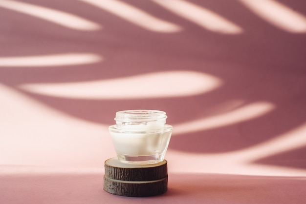 Il barattolo di vetro con crema idratante bianca sulla sega di legno taglia su un fondo rosa. lozione sullo sfondo dell'ombra tropicale di una foglia di palma. il concetto di cura della pelle
