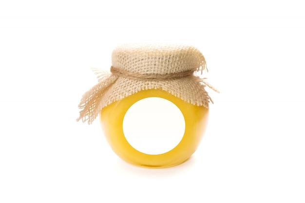 Il barattolo di vetro del miele con l'etichetta in bianco deride su isolato.