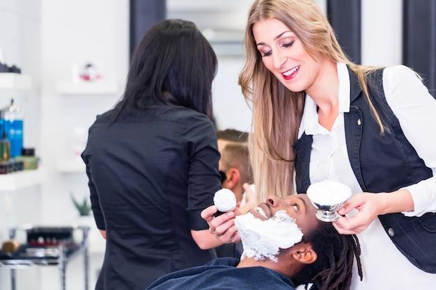 Il barbiere che insapona il cliente si prepara a raderlo