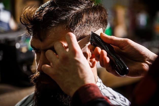 Il barbiere lavora con il tagliacapelli.