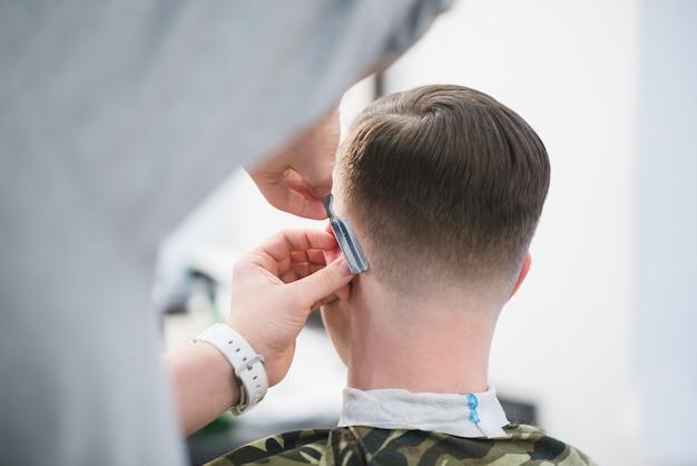 Il barbiere rade il collo del cliente con un rasoio pericoloso. taglio di capelli maschile nel barbiere. il barbiere crea un'acconciatura alla moda
