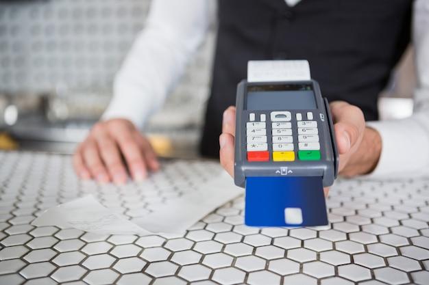 Il barista accetta una carta di credito al bancone del bar