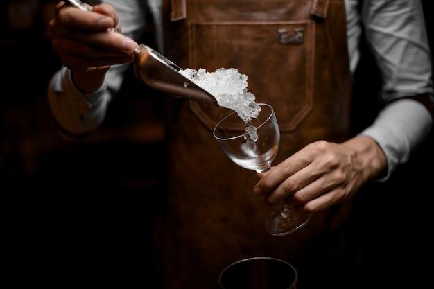 Il barista aggiunge il ghiaccio nel bicchiere da cocktail con la paletta