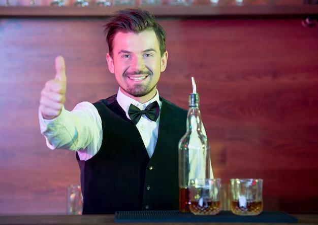 Il barista allegro sta stando in piedi in un vestito e sta mostrando i pollici su