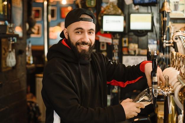 Il barista barbuto sorridente versa la birra in un bicchiere