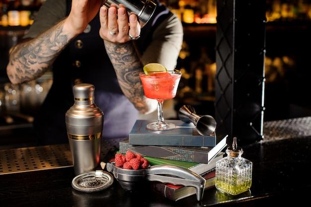 Il barista che produce il cocktail rosso dolce fresco e dolce dell'estate ha sistemato sui libri