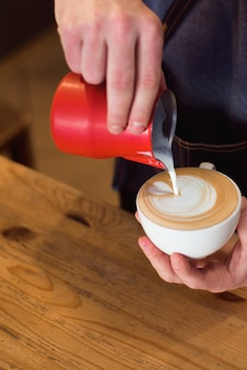 Il barista che versa il latte in tazza di caffè per fare il latte art.