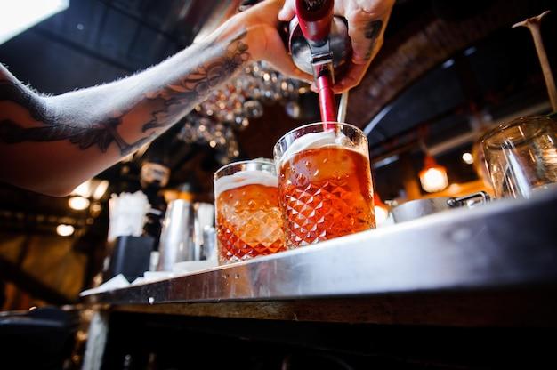Il barista con i tatuaggi versa la birra da una botte in bicchieri