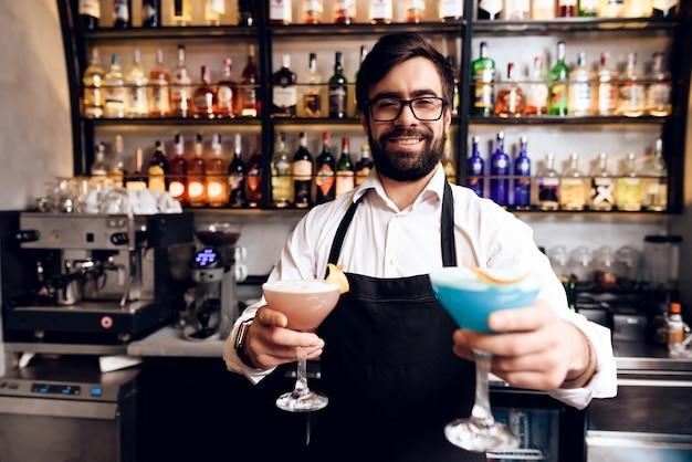 Il barista con la barba ha preparato un cocktail al bar.