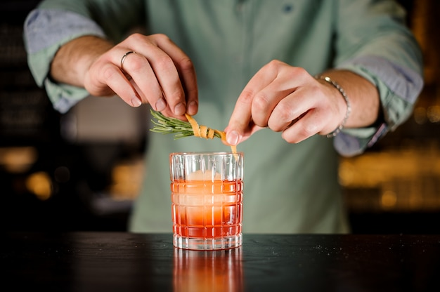 Il barista decora il cocktail con scorza d'arancia e rosmarino