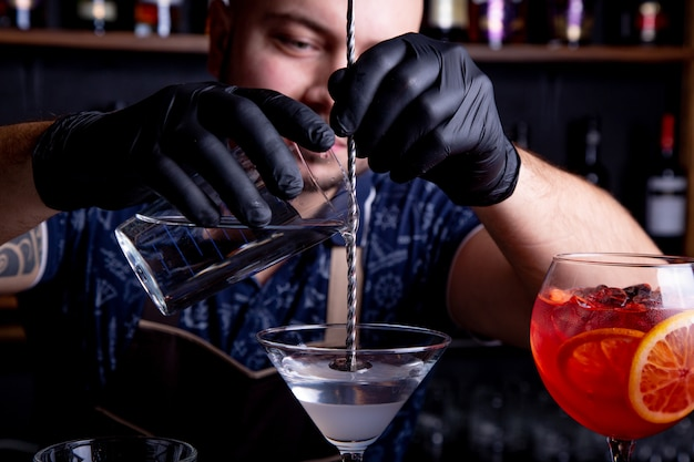 Il barista esperto sta preparando il cocktail al night-club. barista professionista al lavoro nel bar versando la bevanda dolce nel bicchiere sulla festa al night club. barman sta decorando un cocktail.