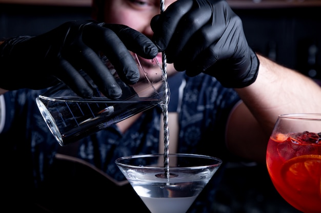 Il barista esperto sta preparando il cocktail al night-club