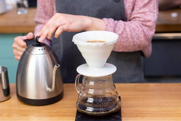 Il barista fa l'espresso usando un imbuto. il processo di preparazione del caffè nel prover.
