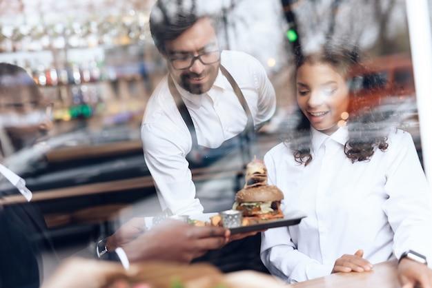 Il barista ha portato un hamburger per una coppia che siede in un bar.