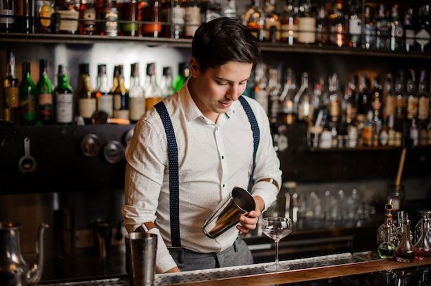 Il barista in camicia bianca sta facendo un cocktail al bancone del bar