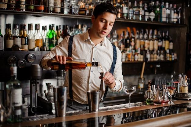 Il barista in camicia bianca sta preparando un cocktail alcolico