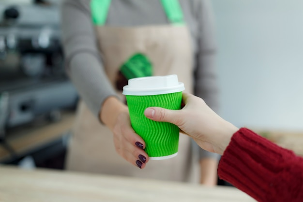 Il barista in grembiule sta offrendo al cliente caffè caldo in una tazza di carta da asporto verde.