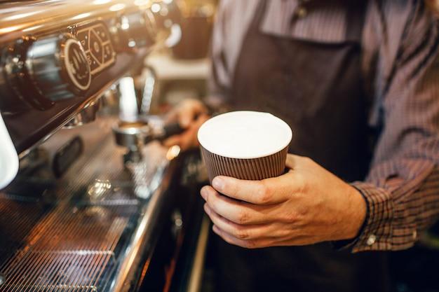 Il barista in grembiule tiene una tazza di caffè con latte galleggiante