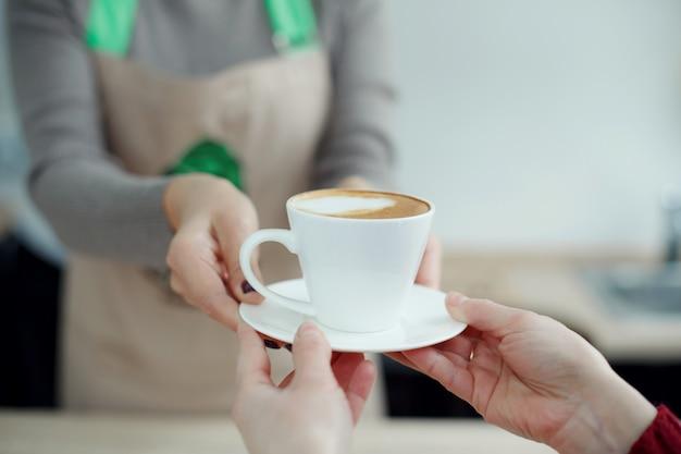 Il barista nella caffetteria dà appena preparato caffè fresco al cliente