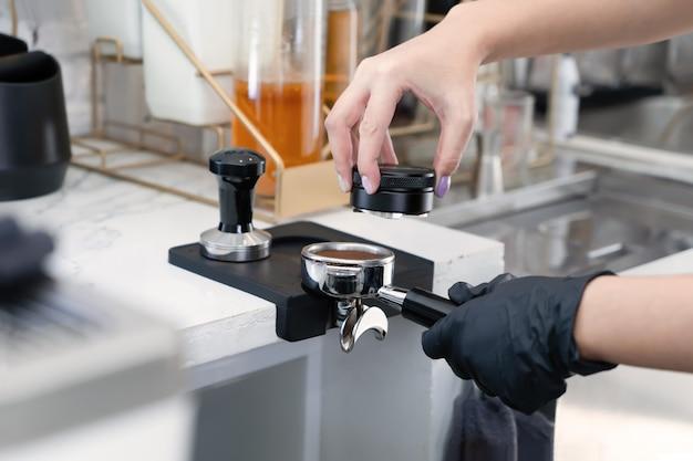 Il barista prepara un caffè con una macchinetta del caffè al bar