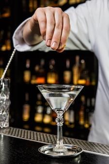 Il barista prepara un cocktail al bar, spremendo una buccia di limone con un drink in un bicchiere da martini