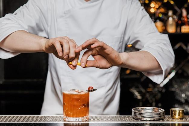 Il barista prepara un cocktail al bar, spremendo una buccia di limone con un drink in un bicchiere di rocce