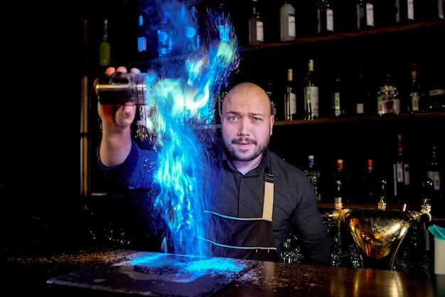 Il barista prepara un cocktail alcolico caldo e accende il bar