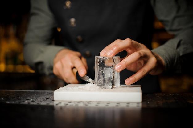 Il barista prepara un grande pezzo rettangolare di ghiaccio