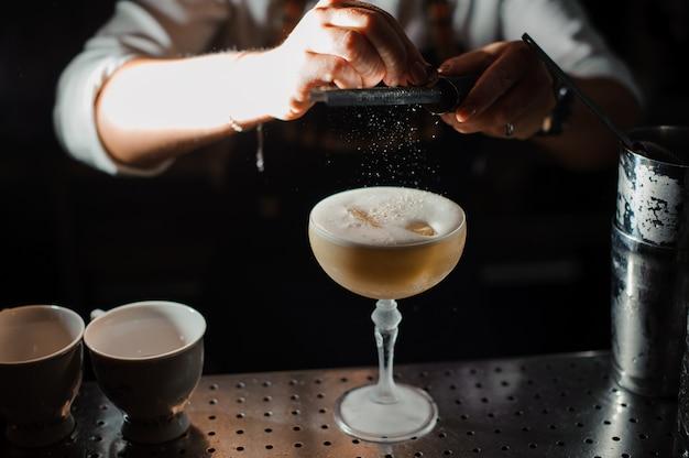Il barista prepara una miscela acida di cocktail alcolici, usando l'attrezzatura da bar