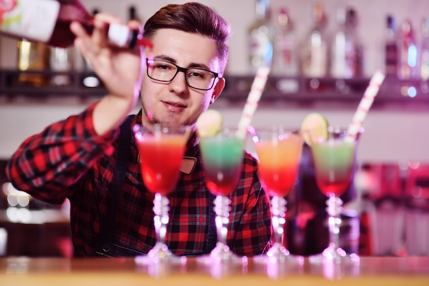 Il barista professionista prepara e mescola cocktail versando lo sciroppo rosso da una bottiglia di un bar in una discoteca