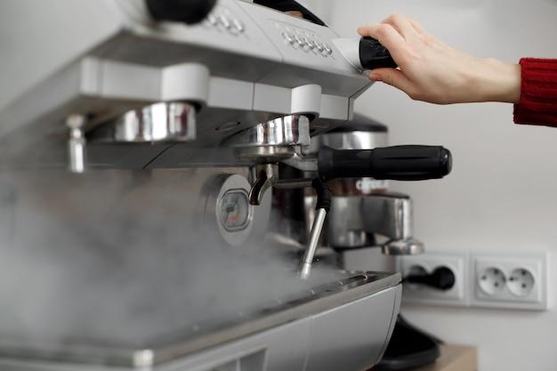 Il barista scarica il vapore del preasure dalla macchina del caffè
