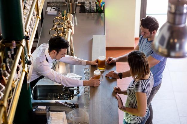 Il barista serve birra in coppia