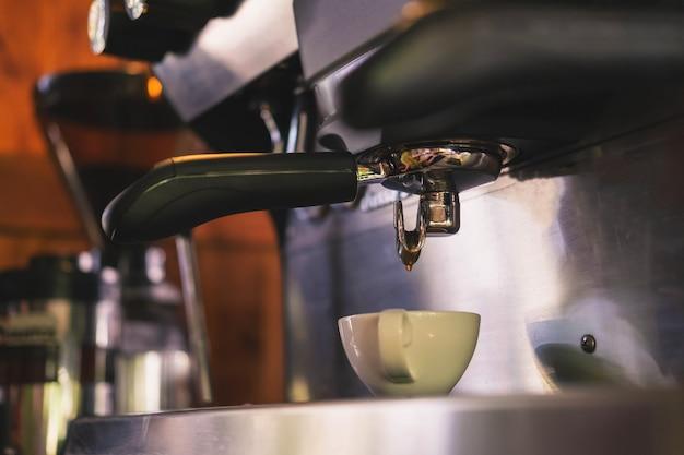 Il barista si prepara a preparare il caffè con una macchina da caffè.