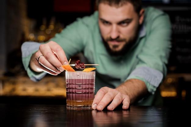 Il barista sta decorando un cocktail con whisky e ciliegia