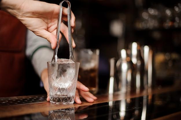 Il barista sta mettendo un ghiaccio in un bicchierino