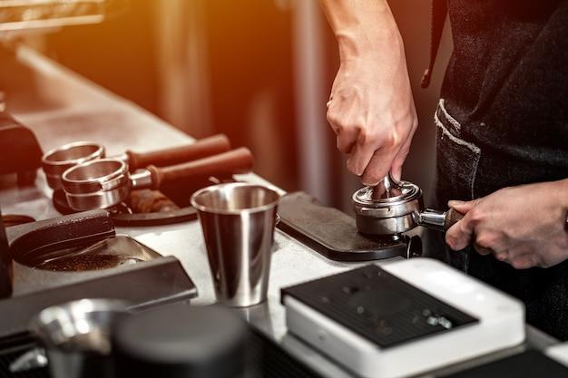 Il barista sta preparando un caffè al bar della macchina.