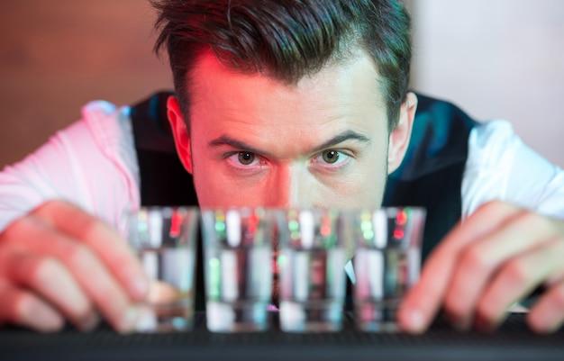 Il barista sta preparando un cocktail al bar per le persone.