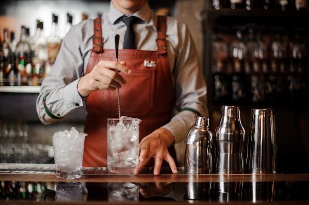 Il barista sta preparando un cocktail con ghiaccio